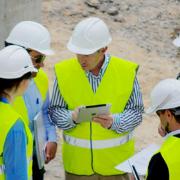Coordinador en la obra con la tablet y la App instalada dirigiendo su equipo.