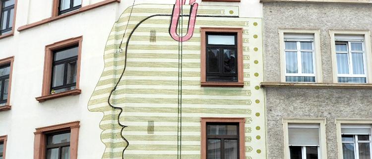 Fachada de un edificio con dos siluetas con forma de rostro sujetas por un clip.