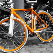 Bicicleta naranja apoyada en una farola