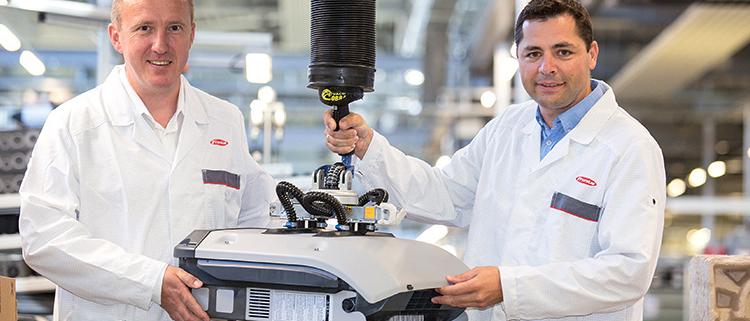 De izquierda a derecha) Jefe de la división de Solar Energy Martín Hackl y miembro del Consejo Thomas Herndler levantan con orgullo el SnapInverter número 100.000 de la línea de producción en Sattledt.